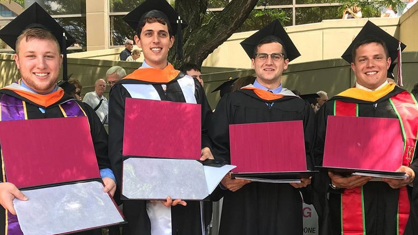 Four men in graduation regalia holding their diplomas as they pose for at commencement.