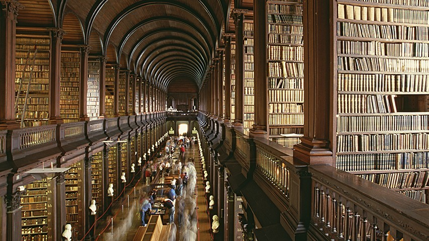 The Long Room at Trinity College, with rows of books and students studying.