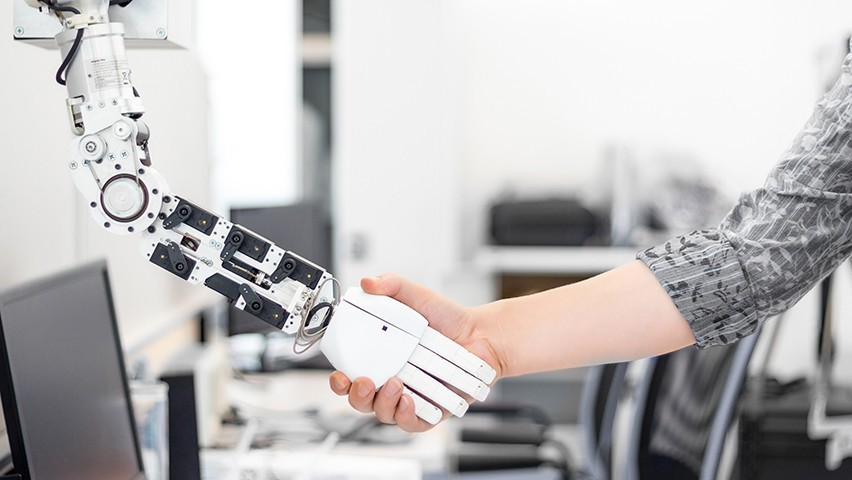 A female shakes hands with a robot in a busy laboratory.