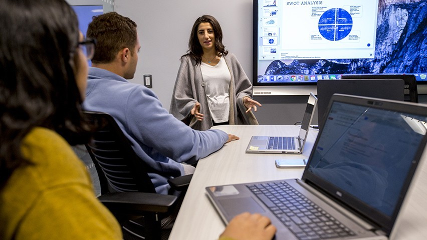 One male and two female students collaborate in a high-tech conference room at Stevens.