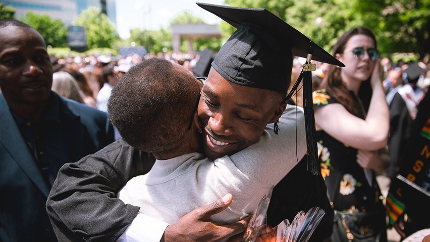 A young man in graduation regalia embraces his mother at commencement.