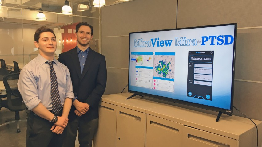 The two students behind MiraView in the Stevens Venture Center alongside a monitor showing their app's capabilities.