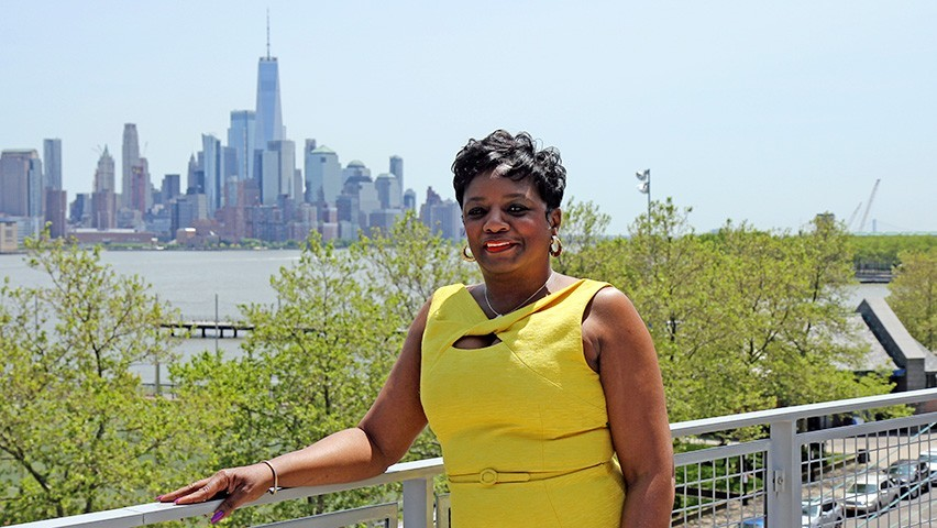 Pam Charleston in a yellow dress with downtown Manhattan in the background.