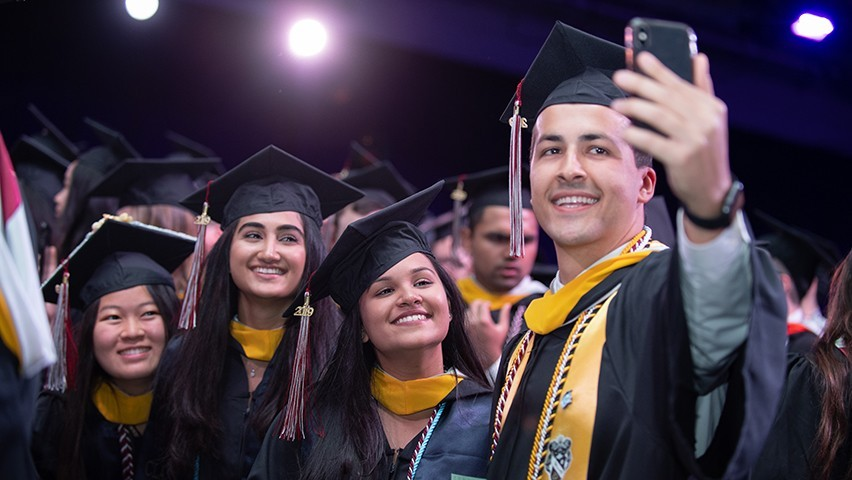 Three female students pose for a selfie taken by a fourth student. All are in their graduation regalia.
