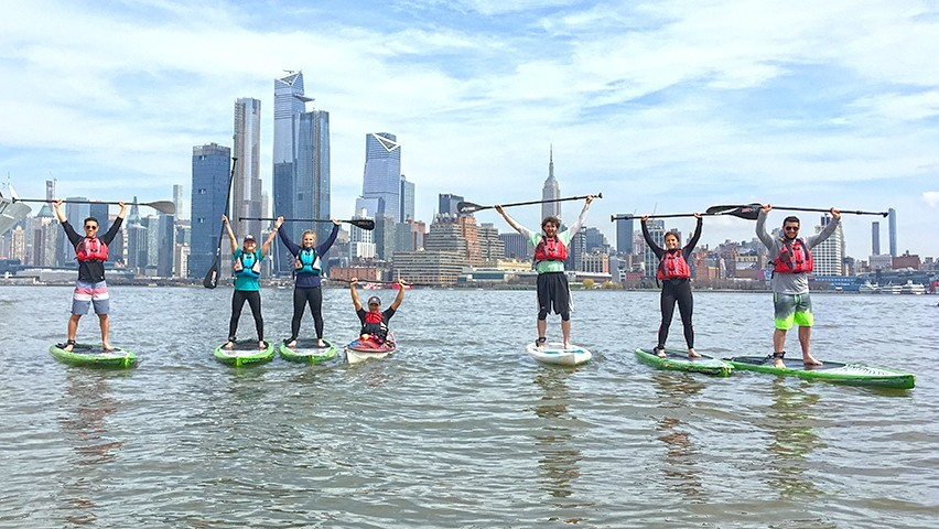 Stevens students on paddleboards on the Hudson River, with the Manhattan skyline in the background.