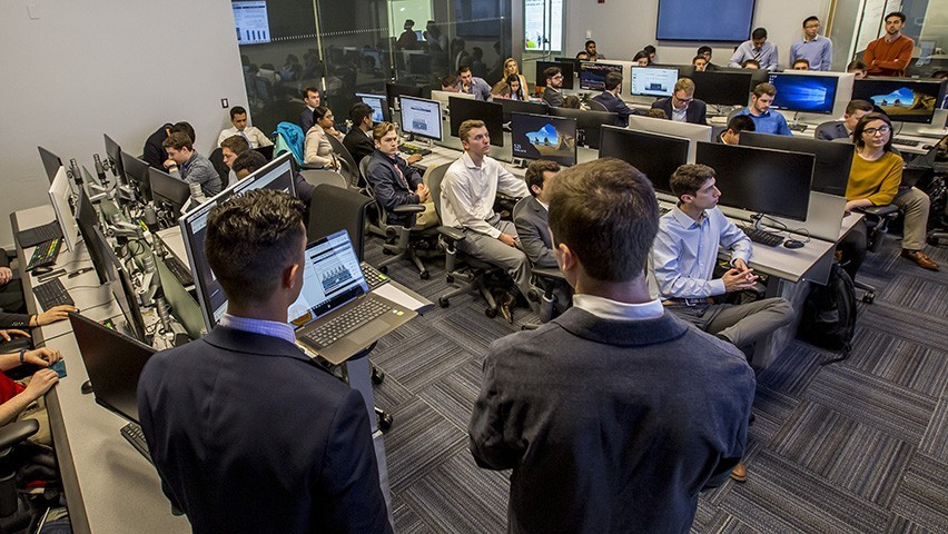 A class in a Bloomberg finance lab being led by two male students wearing dark suits.