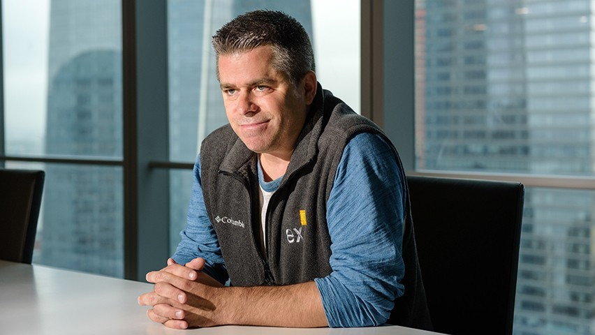 John Schwall in a gray IEX vest and blue shirt at a conference table with the New York City skyline seen through a window.