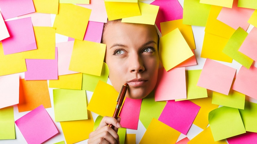 A woman's head surrounded by pink, green, yellow and purple post-it notes