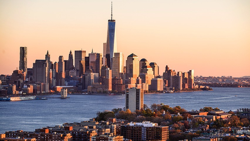 The Stevens campus and downtown New York City skyline at sunset.