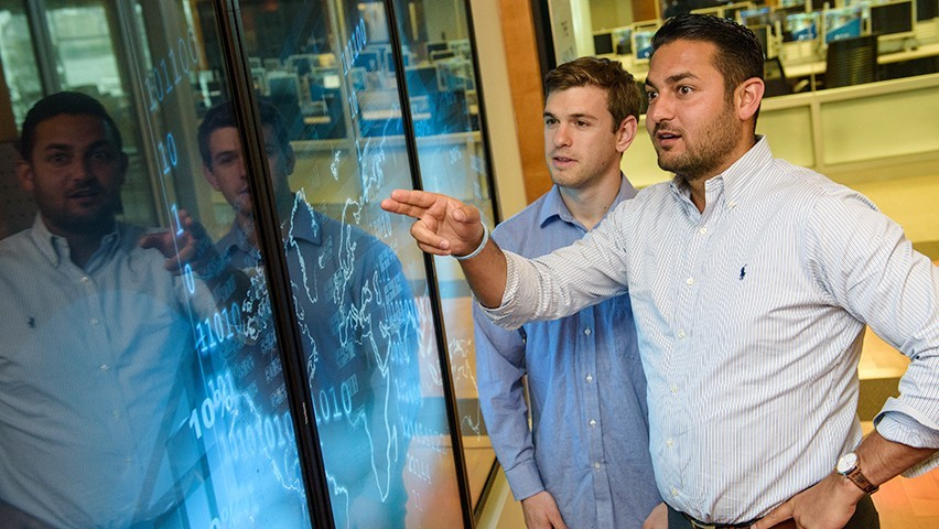 Two students comparing visualizations on a touchscreen in the Babbio Center at Stevens.