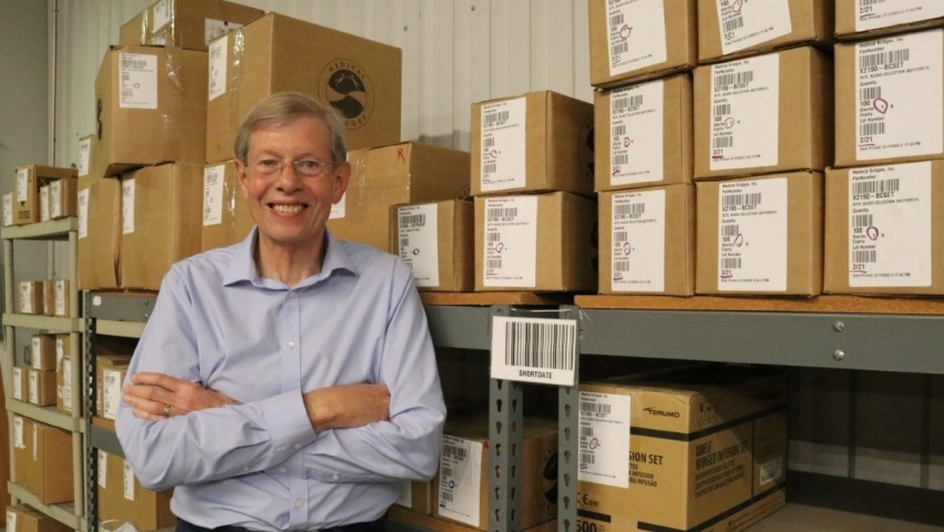 Walter Ulrich '68 posing with stacks of boxes at the nonprofit's warehouse
