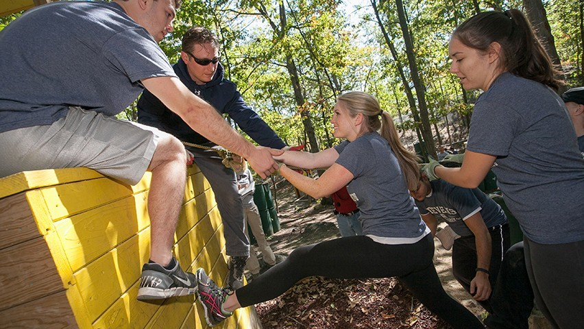 A female student is helped onto an obstacle in the forest course at West Point.