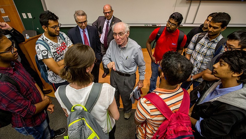 Students surround Josh Weston in a lecture hall after his talk.