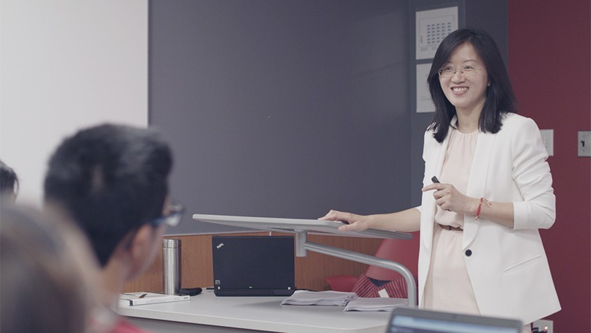 Prof. Ying Wu teaches her international finance class. She's standing in front of the room, answering a student's question.