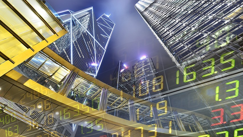 The Hong Kong skyline at night with a stock ticker projected over it.