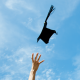 Photo of arm throwing graduation cap in the air