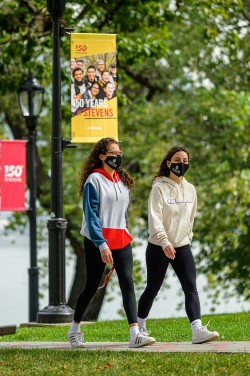 Two female students walking on campus with masks