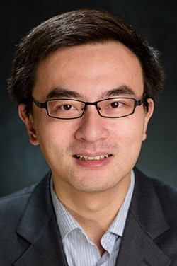 Headshot of Dr. Cui in a dark suit against a dark background.