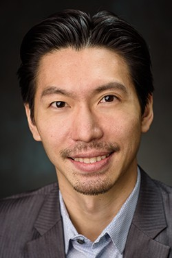 Headshot of Dr. Lin in a gray jacket against a black backdrop.