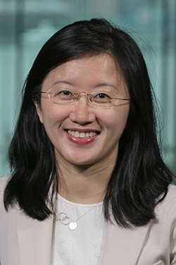 Headshot of Dr. Wu in a light jacket before the Manhattan skyline.