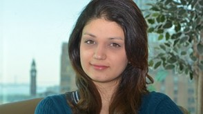 Headshot of Parisa Golbayani in the Babbio Center overlooking New York City