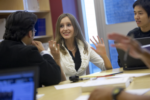 A woman presents her findings to the rest of her team at a conference table.