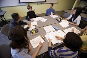 A group of students with their faculty advisor working together around a desk.