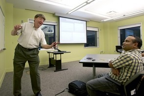 A telecommunications professor demonstrates a point in a graduate class.