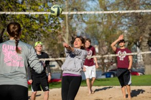 Female and male students playing a game of sand volleyball