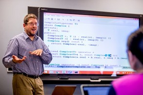 A professor demonstrates a technology innovation lesson to a graduate class.