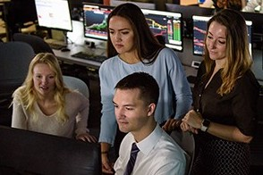 Five students working at a Bloomberg terminal in the Hanlon Lab.
