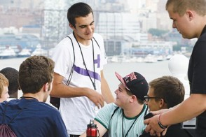 A group of male students get to know one another. The Manhattan skyline is visible in the back.
