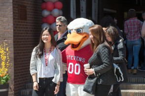 Students standing with the Stevens Duck