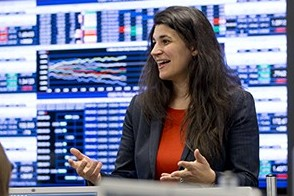 Dr. Eleni Gousgounis, in a dark jacket and red blouse, teaches a class before a screen displaying financial data.