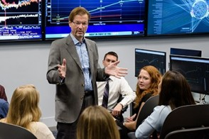 Dr. George Calhoun speaks with a group of students seated at Bloomberg terminals. Screens in the background show live financial data.