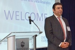 Dr. Ionut Florescu, in a dark suit and red tie, speaks to the audience in front of a welcome screen for the conference.