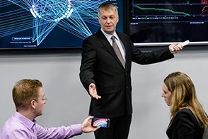 A student uses his phone to introduce data into a lecture as a professor, in a suit, leads class in the lab.