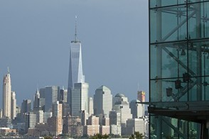 The glass of the Babbio Center in the foreground shows the downtown New York City skyline across the river.