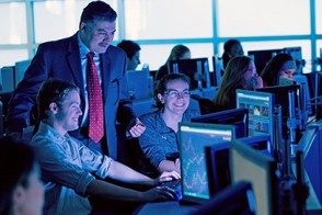 Dr. Khaldoun Hashanah works with a pair of students using Bloomberg terminals in the Hanlon Lab.