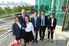 A team of students with their professor about to present a Field Consulting project to a company's leadership.