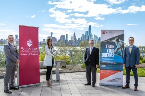 Group photo of leaders from Stevens and representative from Real Madrid Graduate School, standing in front of school banners, outside, with the NYC skyline in the background.