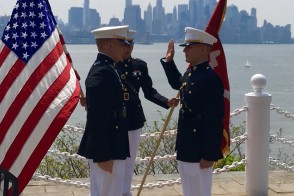 Two servicemen saluting with flags on waterfront