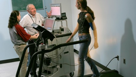 Student walking on a treadmill being monitored in a lab