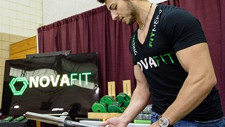A student demonstrates NovaFit's unique weight grips at the Innovation Expo.