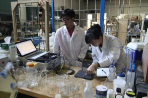 A student and a professor examine a sample in a lab