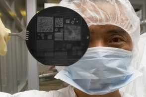 Student in clean suit holding up a sheet of nanocircuits