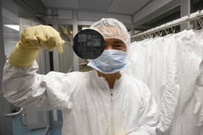 Lab researcher holding chip in clean room