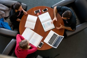 Aerial view of students with textbooks and laptops around a table.