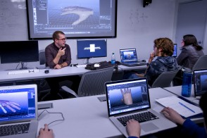 group discussion in lab with digitally rendered hand on screens