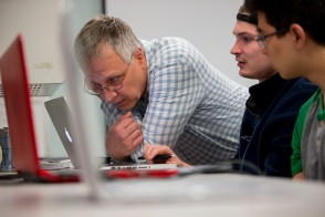 A faculty member with students looking at a computer.